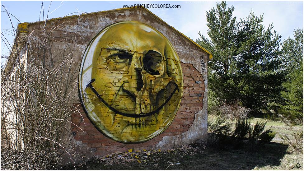 Graffiti happy face and crane by Pinche